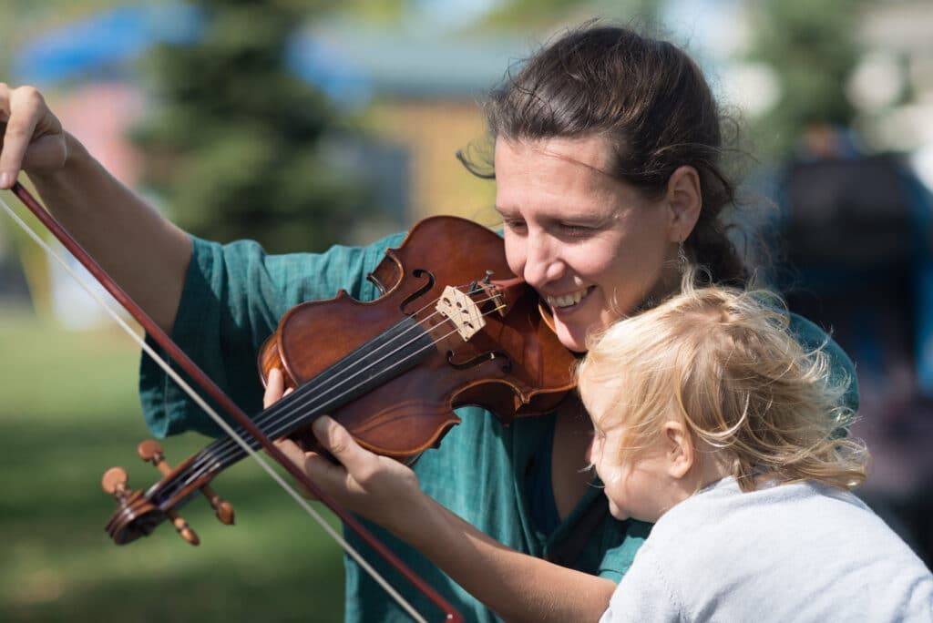 Image of young child watching a woman play the violin